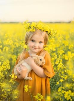 女の赤ちゃんは夏に菜種畑で彼女の腕にウサギを保持します