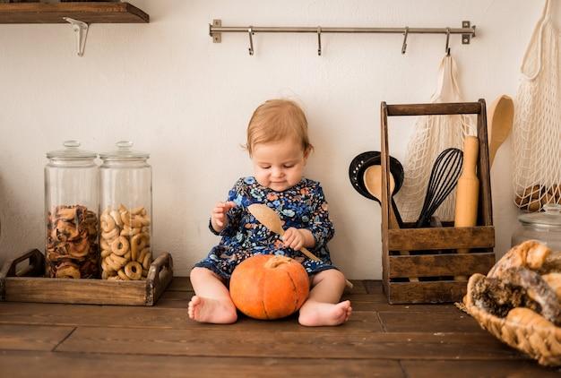 Девочка в голубом платье сидит на деревянной кухне