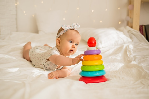 Девочка в цветном боди и повязке на голове играет с пирамидкой на белом одеяле на кровати