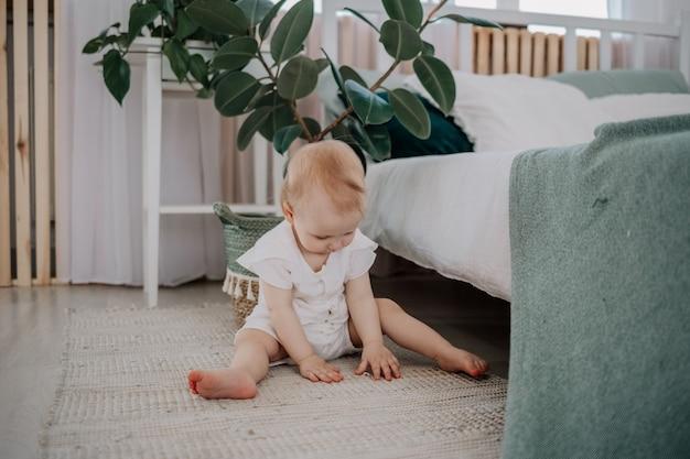 Девочка в кисейном комбинезоне сидит на коврике на полу в спальне