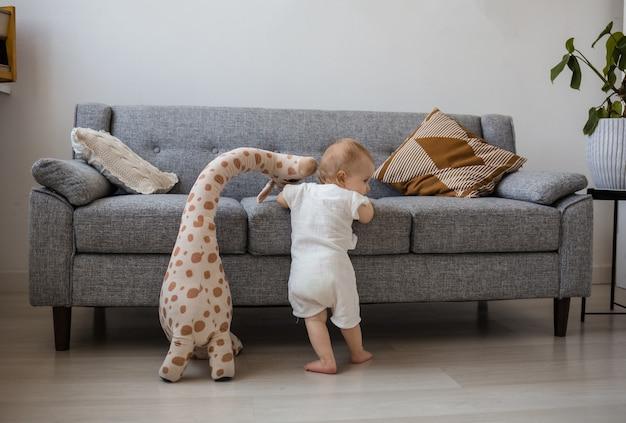モスリンのジャンプスーツを着た女の赤ちゃんが、キリンのぬいぐるみが付いた灰色のソファの横に立っています。