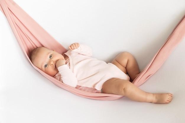 분홍색 바디 수트를 입은 아기 소녀는 흰색 중립 배경에 분홍색 해먹에 누워 손가락을 빨고 있습니다.