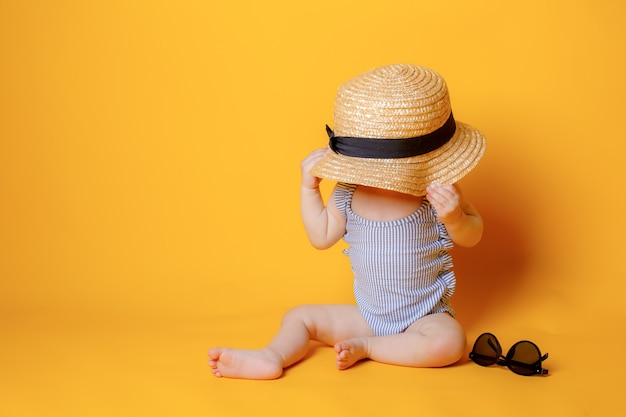 Девочка в купальнике с шляпкой сидит на желтом фоне
