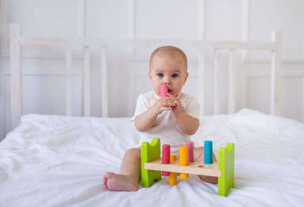 레이스가 달린 흰색 바디수트를 입은 여자 아기가 교육용 장난감을 가지고 침대 위의 흰색 담요에 앉아 있다