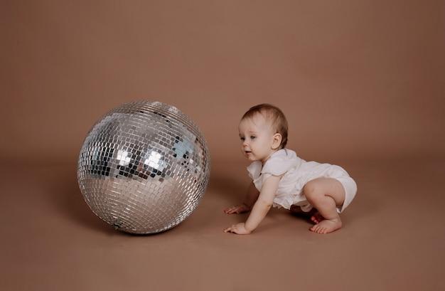 Девочка в белом кисейном комбинезоне ползает с серебряным диско-шаром на бежевом фоне с местом для текста