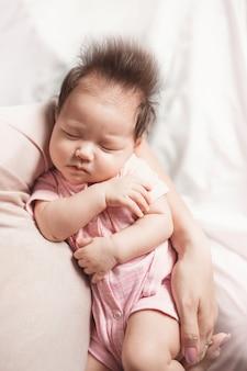 明るい背景に彼女の母親の腕の中で女の赤ちゃん