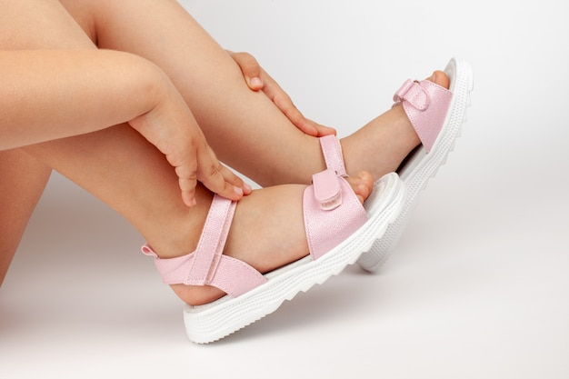 Девочка сидит на белом фоне в розовых блестящих детских сандалиях