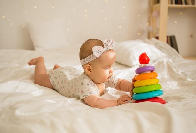 Девочка лежит и играет с пирамидой на белом одеяле на кровати