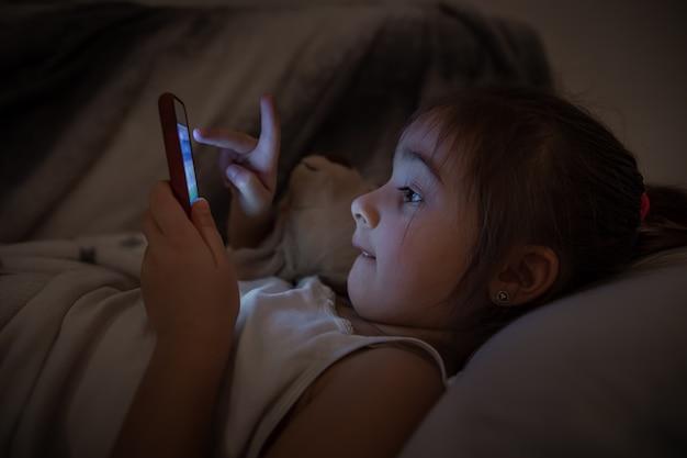 女の赤ちゃんがベッドに横になり、スマートフォンをクローズアップで使用します。漫画やゲームへの子供の中毒の概念。