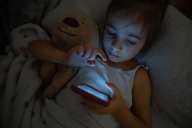 女の赤ちゃんがぬいぐるみを持ってベッドに横になり、スマートフォンを使っています。漫画やゲームへの子供の中毒の概念。