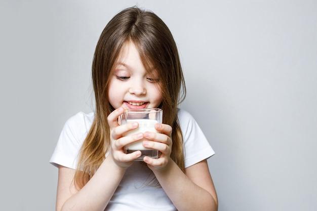 Девочка радостно смотрит на стакан молока