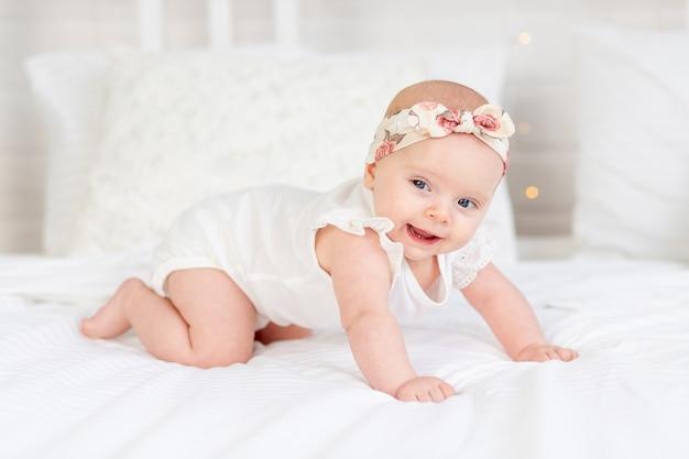 한 여자 아이가 집에 있는 하얀 면 침대에서 미소를 짓거나 웃고 손으로 기어다닌다