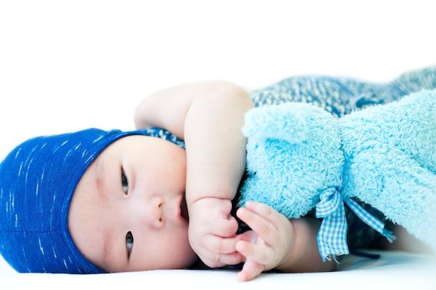 파란 모자와 옷을 입은 아기가 밝게 웃고 놀고 있다