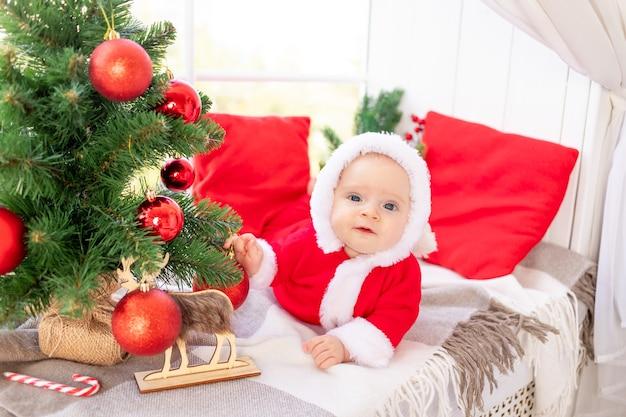 Младенец в костюме деда мороза под елкой играет красными елочными шарами, лежащими на окне дома, концепция нового года