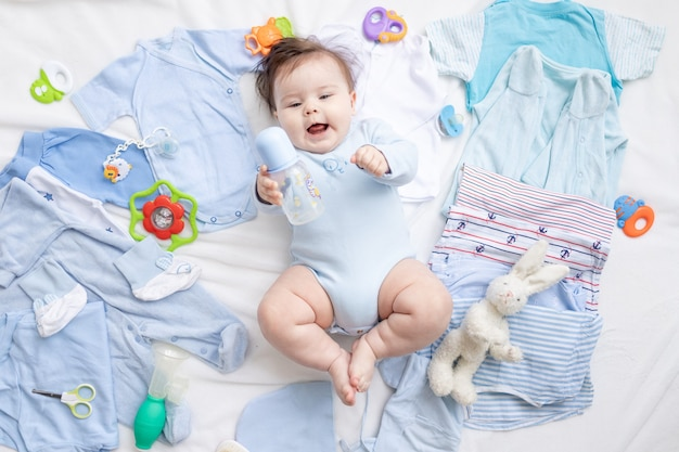 Младенец в синей одежде лежит среди детских аксессуаров и одежды