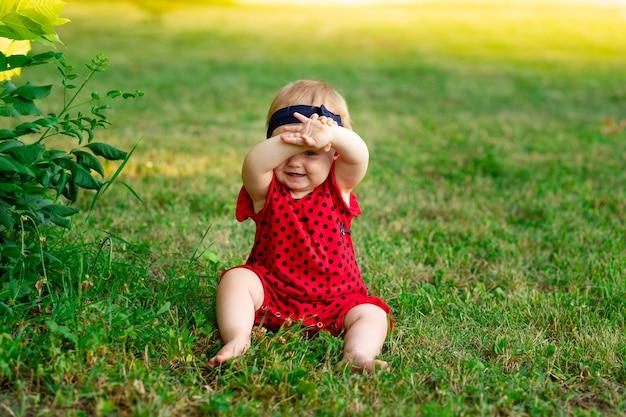 여름에 빨간 바디수트를 입은 푸른 풀밭에 있는 아기가 석양에 숨어 손으로 얼굴을 가렸습니다