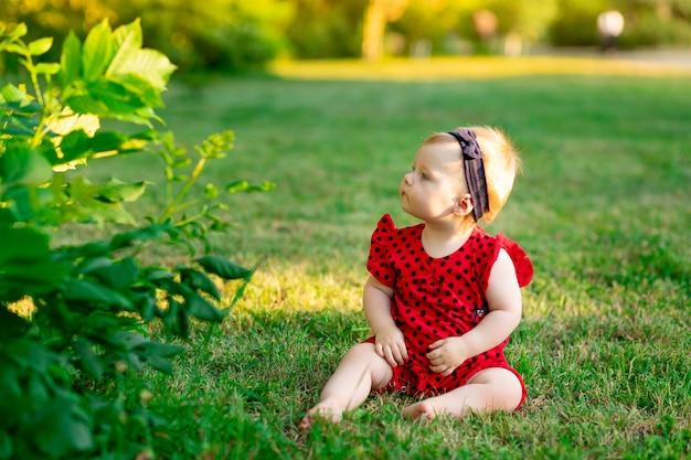 여름에 빨간 바디수트를 입은 푸른 잔디 위에 있는 아기가 석양을 바라보고 있다