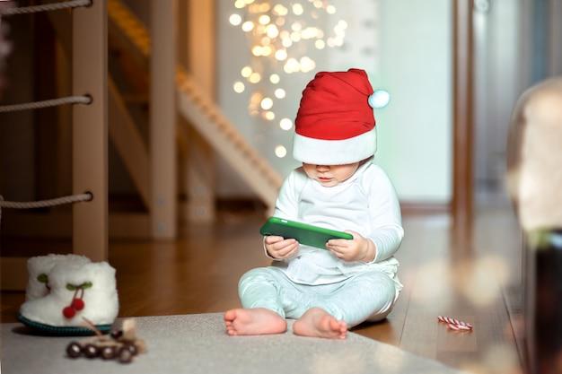 サンタの衣装を着た1歳までの赤ちゃんが、自宅の床に座って興味を持って電話を見ています。