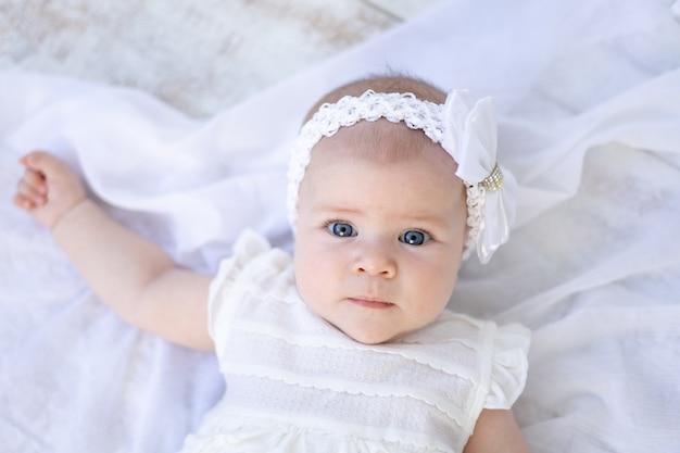 Младенец с голубыми глазами смотрит в камеру
