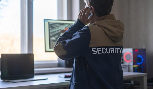 Мужчина-охранник, вид сзади, сидит перед компьютером и проверяет камеру видеонаблюдения онлайн
