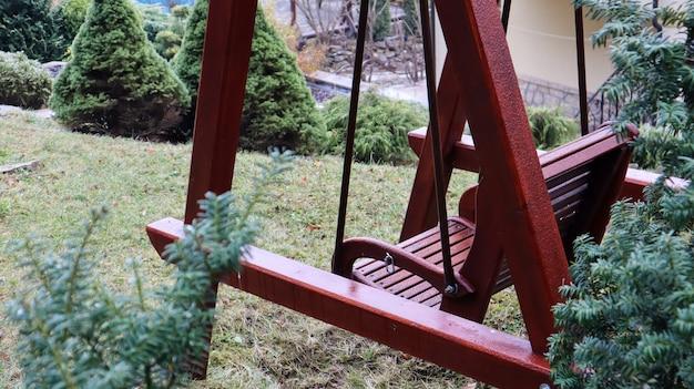Качели на заднем дворе идеально подходят для отдыха. садовые старые деревянные качели на заднем дворе сельского дома.