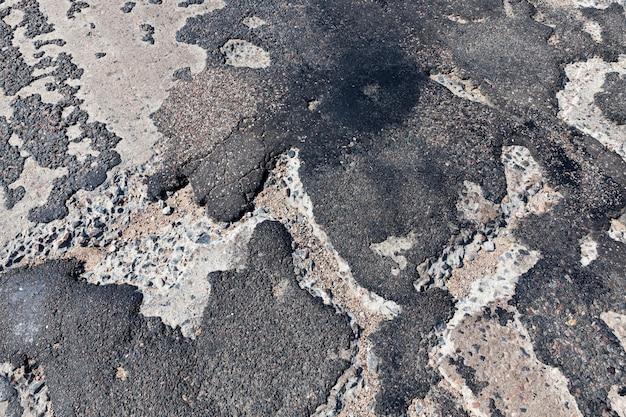 何度も修理された悪いアスファルト道路