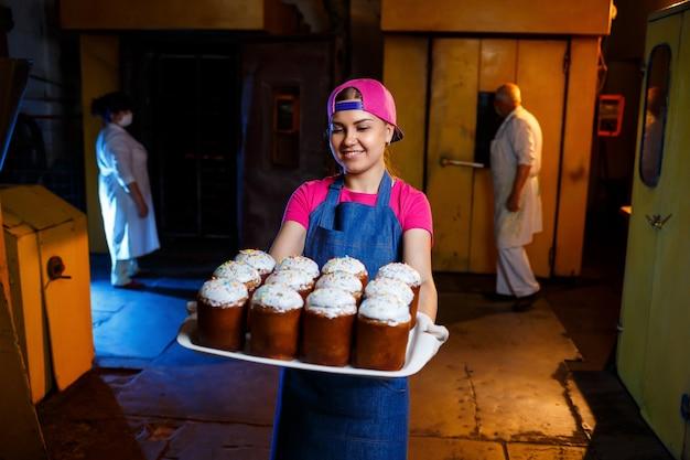 Девушка-пекарь держит поднос с горячей выпечкой в пекарне. производство хлебобулочных изделий. поднос со свежей хрустящей выпечкой.