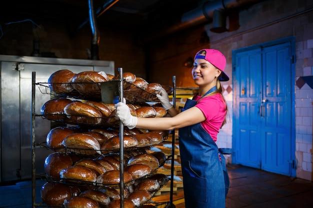 パン屋の女の子は、パンの棚を背景にパン屋で熱いパンを取ります。パンの工業生産。パン屋で焼く段階