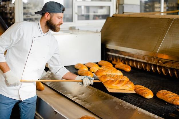 빵 굽는 사람은 나무 삽으로 산업용 오븐에서 뜨거운 빵을 집어 들고 있습니다. 산업용 빵 생산
