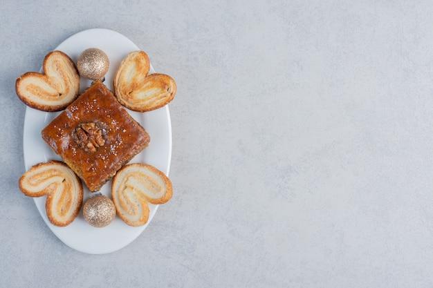 Бахлава и слоеное печенье на блюде с безделушкой на мраморной поверхности