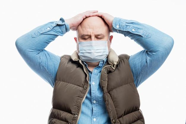 의료 마스크에 대머리 성인 남자는 그의 머리를 보유하고있다. 확대. 코로나 바이러스 전염병 예방 조치.