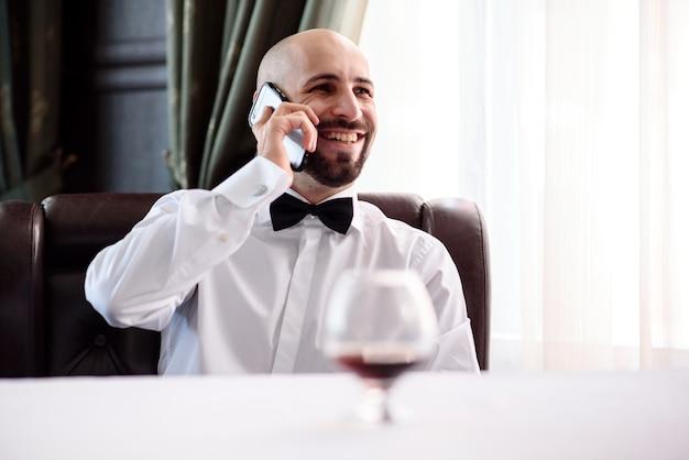 Лысый мужчина в ресторане разговаривает по телефону.