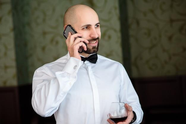 대머리 남자가 레스토랑에서 전화로 말합니다.