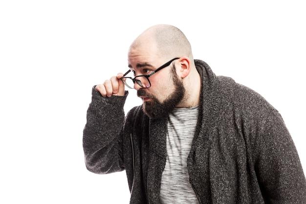 眼鏡とあごひげを生やしたハゲ男は驚いています。白い壁に分離されました。