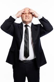 엄격한 검은 양복을 입고 스트레스를 받는 대머리 중년 남성이 손으로 머리를 잡고 있습니다. 비즈니스 문제입니다. 흰색 배경. 세로.