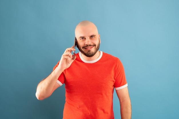 수염을 가진 대머리 중년 남자와 파란색 벽에 빨간 티셔츠. 손에 휴대 전화를 들고 다른 손의 손가락으로 가리 킵니다.