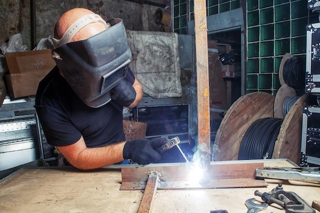 黒い溶接マスクを着たハゲの強い男が、暗い古いガレージで溶接機を使って金属溶接機を醸造している