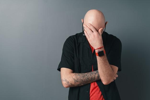 손으로 이마를 만지고있는 동안 문제를 예상하는 회색에 포즈를 취하는 대머리 세련된 남자.
