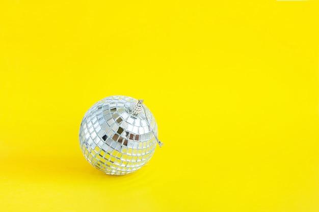 黄色のモノクロの背景にディスコミラーピースのボール
