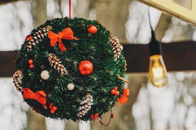 장난감, 소나무 콘 및 활로 장식 된 전나무 가지의 공.
