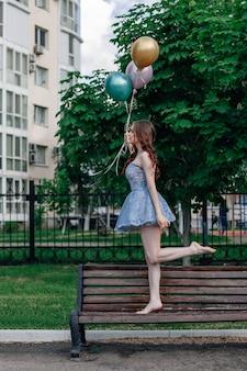 コルセットドレスを着たバレリーナが、風船を手に持って公園のベンチでつま先で歩く