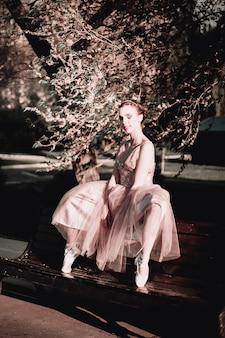 Балерина в длинном розовом платье сидит на спинке скамейки, широко расставив ноги ...