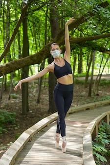 마스크와 포인트 슈즈를 입은 발레리나가 삼림 공원의 나무 길에서 운동을하고 있습니다. 안전한 야외 훈련 개념