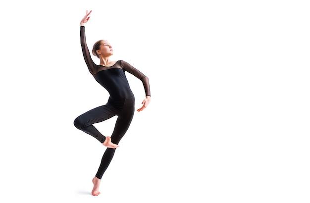 Балетная девушка в черном облегающем костюме танцует на белом пространстве в современной современной хореографии.