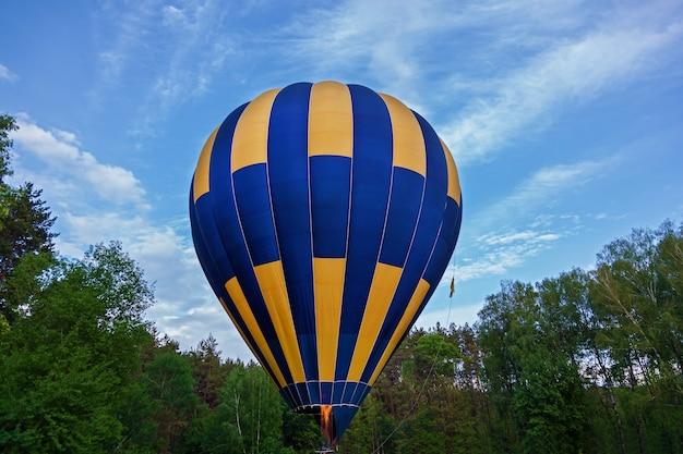 熱気球で満たされた飛行の準備ができているバスケット付きの気球。飛行用気球の準備。風船まつり