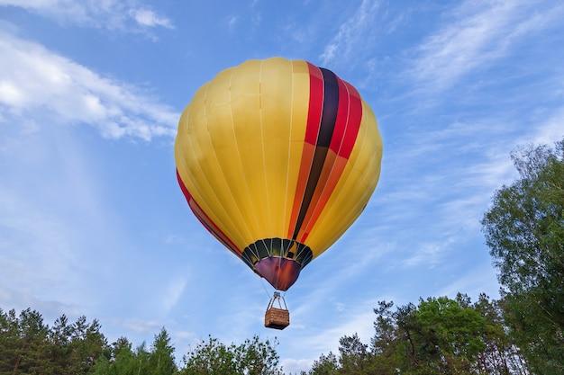 熱気球が入った気球が青い空を飛んでいます。青い空に浮かぶ気球。風船の祭典