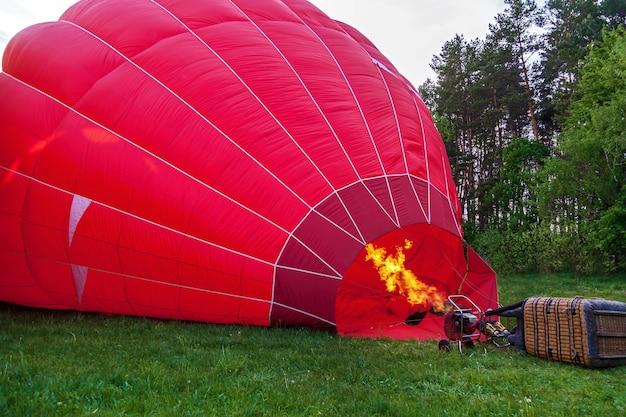 かご付きの気球が地面にあり、気球を冷気と熱気で満たすための機器です。気球を打ち上げる準備をしています。