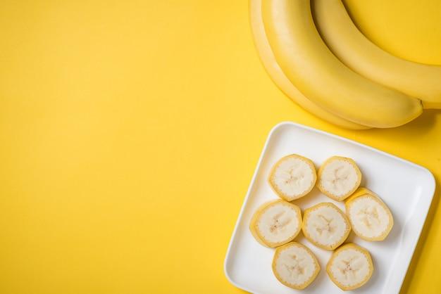 Банч бананов и нарезанный банан в блюде на желтом фоне.
