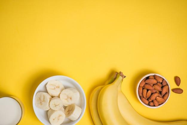 노란색 배경 위에 접시에 바나나 한 뭉치와 얇게 썬 바나나.