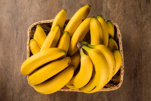 テーブルの上の鍋にバナナの束とスライスしたバナナ。